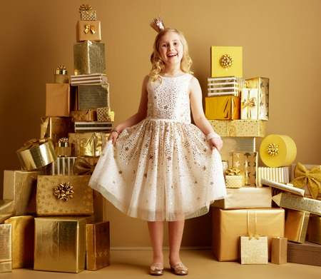 Full length portrait of happy modern child in beige fit and flare dress and a little crown on head among 2 piles of golden gifts in front of a plain wall. holidays shopping illustration. Stock Photo