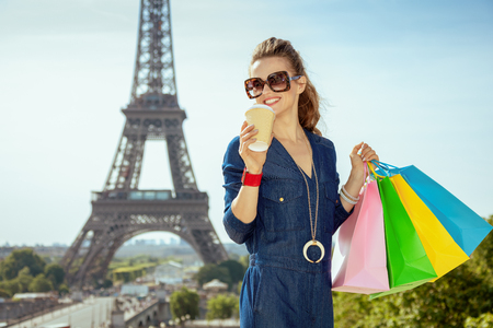 smiling elegant traveller woman in blue jeans overall with shopping bags and coffee cup at Trocadero overlooking Eiffel tower in Paris, France.