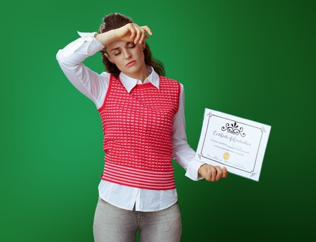 tired young student woman in grey jeans and pink sleeveless shirt with Certificate of Graduation isolated on chalkboard green background. Difficult and expensive education does not guarantee future