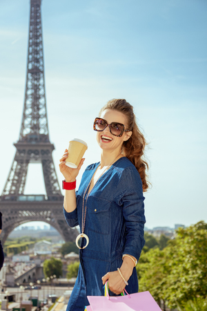 Portrait of smiling stylish woman in blue jeans overall with shopping bags and coffee cup in the front of Eiffel tower in Paris, France.