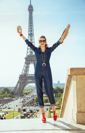 Full length portrait of smiling stylish tourist woman in blue jeans overall with coffee cup and baguette rejoicing against clear view of the Eiffel Tower in Paris, France.