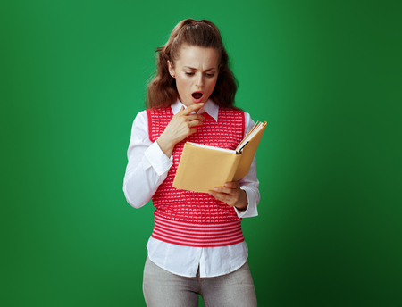 surprised modern learner woman in grey jeans and pink sleeveless shirt reading a yellow book against green background. Banco de Imagens