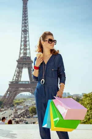 smiling stylish woman in blue jeans overall with shopping bags and coffee cup at Trocadero overlooking Eiffel tower in Paris, France.