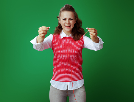 smiling healthy learner woman in grey jeans and pink sleeveless shirt giving headphones against green background. Modern education with listening to audio materials. Technology advancement.