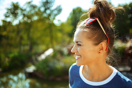 smiling young traveller woman in blue t-shirt on river boat exploring countryside while having river cruise.
