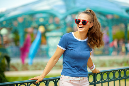 smiling trendy woman in blue t-shirt in theme park looking into the distance.