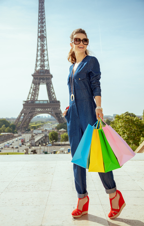 Full length portrait of smiling stylish traveller woman in blue jeans overall with shopping bags looking into the distance in the front of Eiffel tower in Paris, France. Stock Photo
