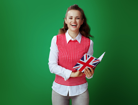 happy modern student woman in grey jeans and pink sleeveless shirt looking through records of English class in United Kingdom flag coloured notebook on chalkboard green background. Banco de Imagens