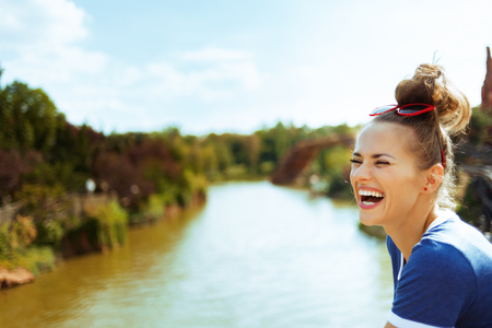 smiling healthy woman in blue t-shirt on river boat having fun time while river cruising.