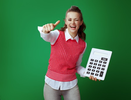 smiling healthy learner woman in grey jeans and pink sleeveless shirt with big white calculator showing thumbs up on chalkboard green background. Expenditures of modern education under control Stock fotó - 117984188