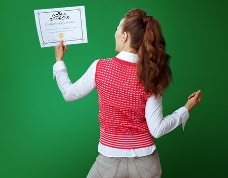 Seen from behind healthy student woman in grey jeans and pink sleeveless shirt rejoicing looking at Certificate of Graduation isolated on green.