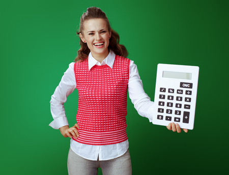 smiling healthy learner woman in grey jeans and pink sleeveless shirt showing big white calculator isolated on green background. finances and expenditures of modern education. Stock fotó