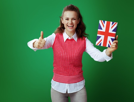 smiling healthy student woman in grey jeans and pink sleeveless shirt with United Kingdom flag coloured notebook showing thumbs up against green background. English language courses or stationary ads.