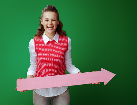 smiling young learner woman in grey jeans and pink sleeveless shirt holding big pink arrow pointing right isolated on green. Banco de Imagens - 117984271