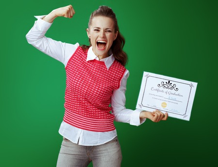 smiling healthy student woman in grey jeans and pink sleeveless shirt with Certificate of Graduation showing biceps on chalkboard green background.