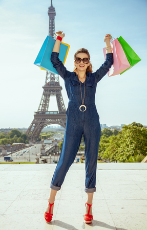 Full length portrait of happy modern woman in sunglasses and blue jeans overall rejoicing with shopping bags not far from Eiffel tower in Paris, France.