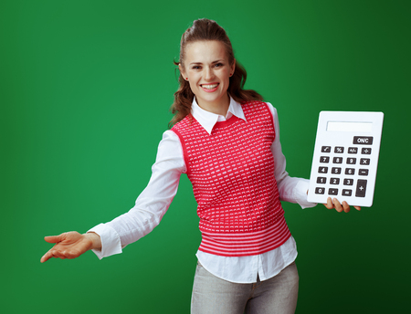 happy healthy student in grey jeans and pink sleeveless shirt with big white calculator inviting isolated on chalkboard green background. Finances and expenditures of modern education under control Stock fotó - 117984311