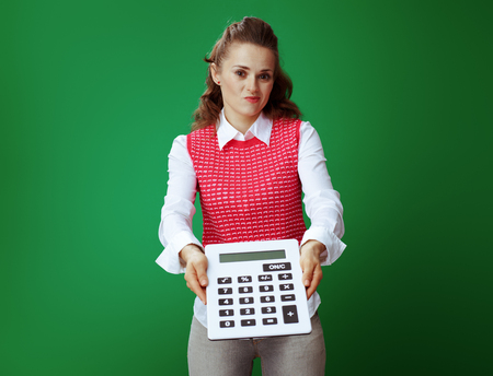 doubting young student woman in grey jeans and pink sleeveless shirt giving big white calculator isolated on green. Financial challenges and expenditures of modern education.