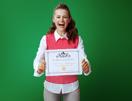 smiling young student woman in grey jeans and pink sleeveless shirt showing Certificate of Graduation against chalkboard green background.