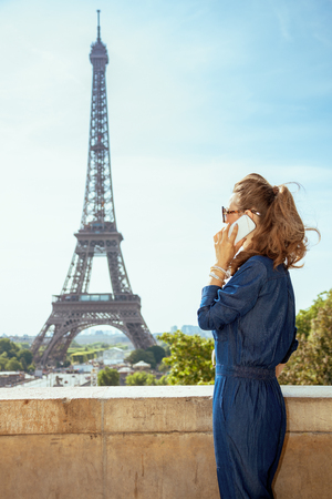 Seen from behind modern tourist woman in blue jeans overall talking on a smartphone against Eiffel tower in Paris, France. Stock Photo