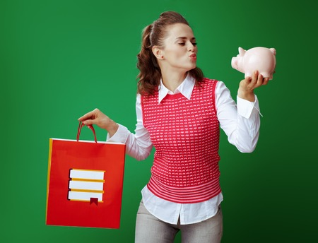 fit student woman in grey jeans and pink sleeveless shirt with red shopping bag with books giving air kiss to pink piggy bank on chalkboard green background. budget bookstore or stationery store