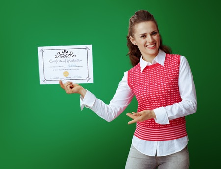 smiling modern learner woman in grey jeans and pink sleeveless shirt showing Certificate of Graduation isolated on chalkboard green.