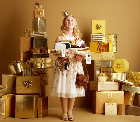 Smiling modern child in beige fit and flare dress and a little crown on head with a great bunch of purchaisings looking up at copy space among 2 piles of golden gifts in front of a plain wall.