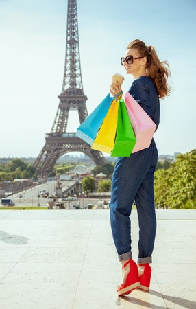 happy trendy traveller woman in blue jeans overall with shopping bags and coffee cup at Trocadero overlooking Eiffel tower in Paris, France.