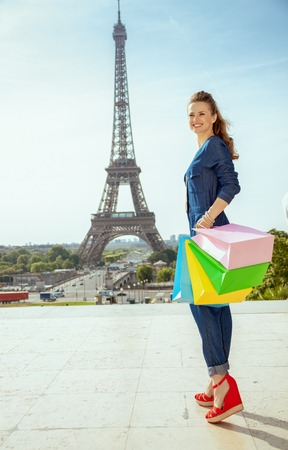 Full length portrait of smiling modern traveller woman in blue jeans overall with shopping bags not far from Eiffel tower in Paris, France.