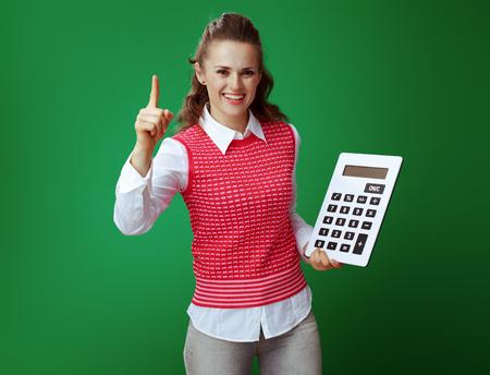 smiling healthy student in grey jeans and pink sleeveless shirt with big white calculator draws attention to something isolated on chalkboard green. Finances and expenditures of modern education. Stock fotó - 117984447