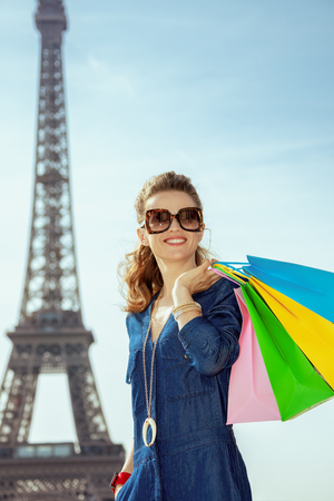 happy elegant woman in sunglasses and blue jeans overall with shopping bags at Trocadero overlooking Eiffel tower in Paris, France. Stock Photo