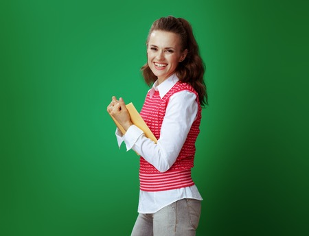 happy modern learner woman in grey jeans and pink sleeveless shirt holding a yellow book on green background.