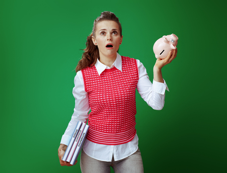 shocked modern learner woman in grey jeans and pink sleeveless shirt with textbooks shaking pink piggy bank and looking up on green background. Financial challenges and expenditures Stock fotó - 117984460