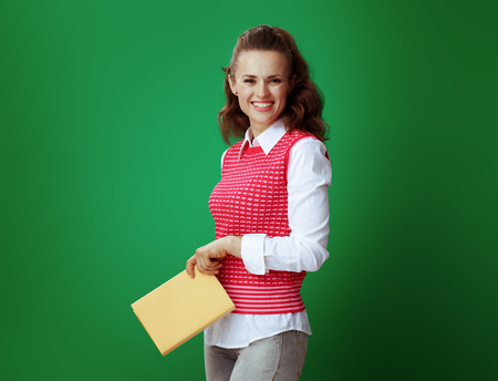 smiling healthy student in grey jeans and pink sleeveless shirt holding a yellow book against chalkboard green background. Good fiction book, textbook, reference educational materials