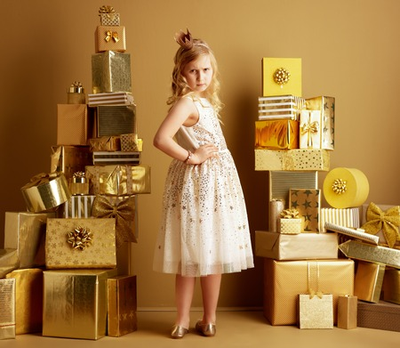 Full length portrait of sad modern child in beige fit and flare dress and a little crown on head among 2 piles of golden gifts in front of a plain wall looking back. birthday illustration.