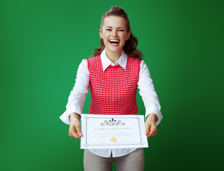 smiling modern student woman in grey jeans and pink sleeveless shirt showing Certificate of Graduation against green background.