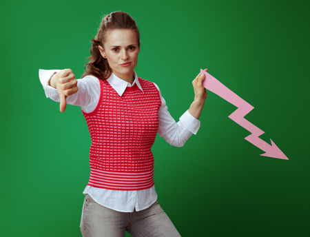 sad fit learner woman in grey jeans and pink sleeveless shirt with falling down graphics arrow showing thumbs down isolated on chalkboard green. Economy study Foto de archivo - 117984513