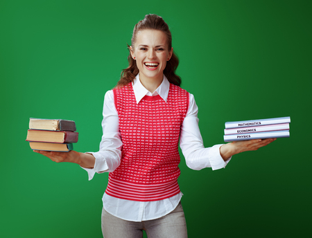 smiling fit student in grey jeans and pink sleeveless shirt showing old and new textbooks against chalkboard green background. Old vs new knowledge concept. Modern educational reforms