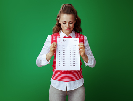unhappy fit learner woman in grey jeans and pink sleeveless shirt holding F exam result against chalkboard green background.