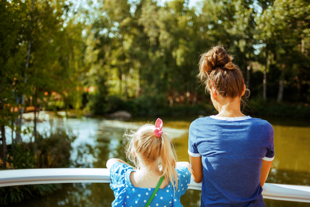 happy young mother and daughter travellers on river boat exploring countryside while on river cruise.