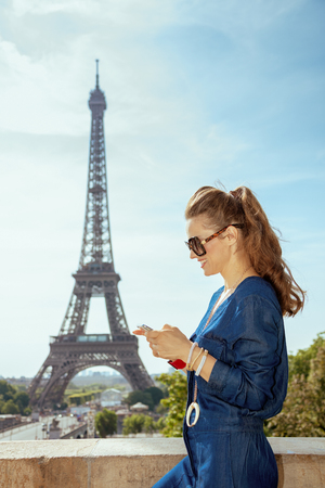 happy stylish woman in blue jeans overall in the front of Eiffel tower in Paris, France watching video in internet via mobile phone.