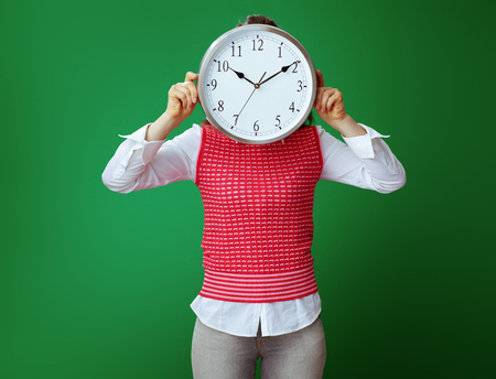fit student woman in grey jeans and pink sleeveless shirt hiding behind white round clock isolated on chalkboard green. Time Management. Stok Fotoğraf - 117984524