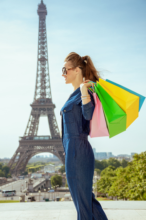 happy young tourist woman in blue jeans overall with shopping bags looking into the distance at Trocadero overlooking Eiffel tower in Paris, France.