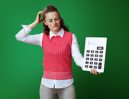 doubting healthy student in grey jeans and pink sleeveless shirt looking at big white calculator isolated on green. Financial challenges and expenditures of modern education.