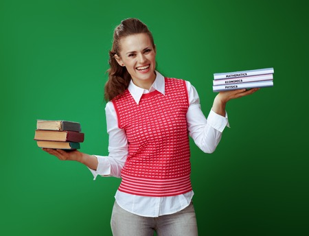 happy healthy learner woman in grey jeans and pink sleeveless shirt weighs old and new textbooks isolated on chalkboard green. Old vs new knowledge concept. Modern educational reforms
