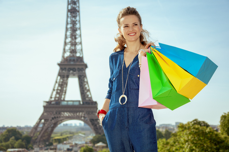 happy young woman in blue jeans overall with shopping bags looking into the distance against Eiffel tower in Paris, France.