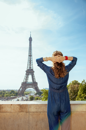 Seen from behind trendy tourist woman in blue jeans overall against Eiffel tower in Paris, France.