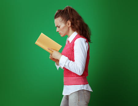 healthy learner woman in grey jeans and pink sleeveless shirt reading a yellow book isolated on green.