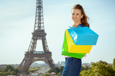 Portrait of happy stylish woman in blue jeans overall with shopping bags against Eiffel tower in Paris, France.