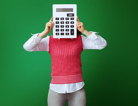 modern student in grey jeans and pink sleeveless shirt hiding behind big white calculator isolated on green. Finances and expenditures of modern education. Stock fotó - 117810039